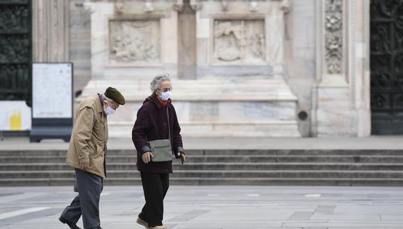 Dos personas caminan en Milán, Italia, durante el confinamiento por el COVID-19. (Foto: MIGUEL MEDINA / AFP)