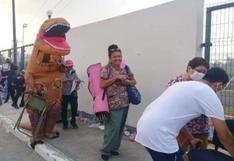 Joven se viste de dinosaurio para acompañar a su mamá a vacunarse en México