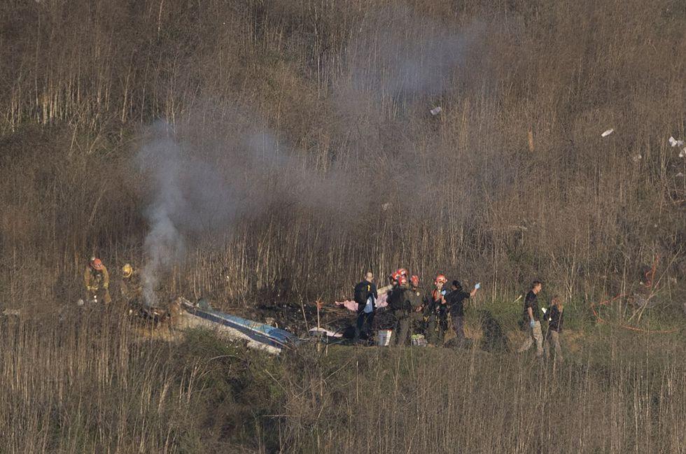 Los bomberos y el personal forense verifican los restos en el lugar del accidente del helicóptero de Kobe Bryant, quien falleció junto a su hija de 13 años y otras siete personas (Foto: AFP)