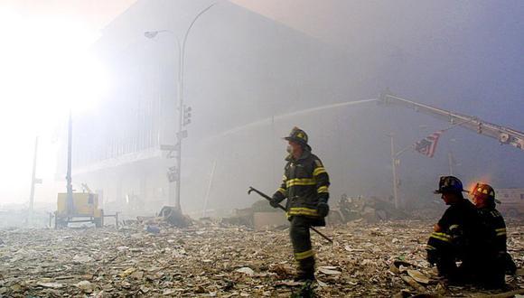 En esta foto de archivo, un bombero camina entre los escombros de las torres gemelas del World Trade Center mientras una bandera estadounidense cuelga de un semáforo el 11 de septiembre de 2001 en Nueva York. (Foto: DOUG KANTER / AFP)