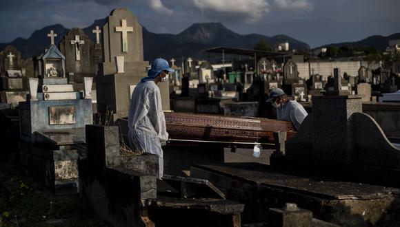En esta foto de archivo del 18 de junio de 2021, trabajadores llevan el ataúd que contiene los restos de Irodina Pinto Ribeiro, de 89 años, quien murió por complicaciones relacionadas con el coronavirus, en el cementerio de Inhauma en Río de Janeiro, Brasil.  (AP/Bruna Prado).