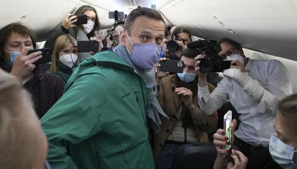 En esta fotografía de archivo del 17 de enero de 2021, Alexei Navalny está rodeado por periodistas dentro del avión antes de su vuelo a Moscú en el Aeropuerto Berlin Brandenburg (BER) en Schoenefeld, cerca de Berlín, Alemania. (AP/Mstyslav Chernov).