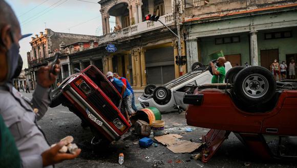 Carros de la policía de Cuba que fueron volcados por los manifestantes en una calle de La Habana. (YAMIL LAGE / AFP).