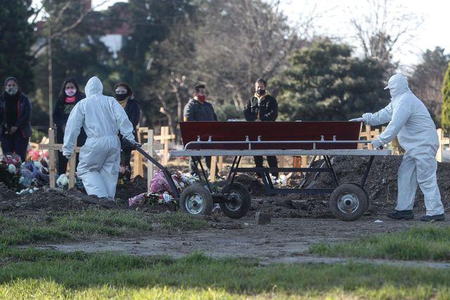 Empleados del cementerio de Flores trasladan un ataúd bajo los protocolos instaurados debido a la pandemia por COVID-19. (EFE/Juan Ignacio Roncoroni).