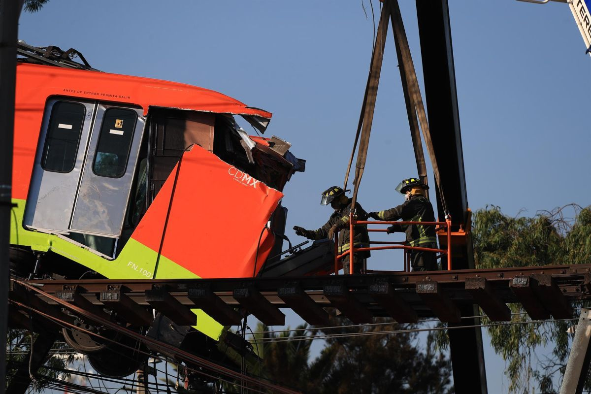 Firefighters remove one of the subway cars on line 12 that crashed in Mexico City. (Photo: EFE / Carlos Ramírez).