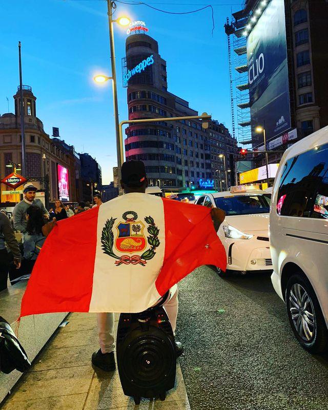 """Juan Diego recorriendo junto a """"timberita"""" las calles de Madrid con la bandera de Perú. (Foto: Facebook / Madrid Timbera)"""