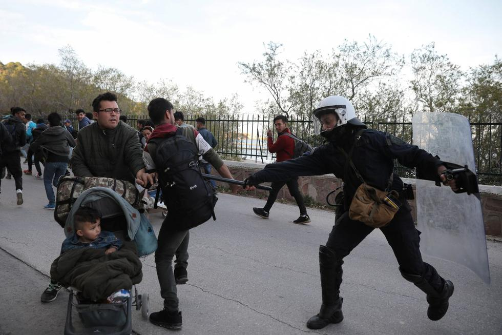Un policía antidisturbios golpea a un migrante con su porra mientras la policía intenta dispersar a un grupo de migrantes fuera del puerto de Mitilene, Grecia. (Foto: Reuters)