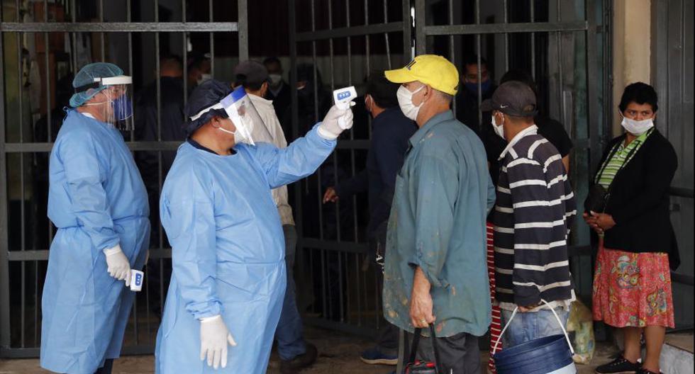 Los trabajadores del Ministerio de Salud toman la temperatura de un guardia, medida contra la propagación del coroanvirus, mientras los familiares de los reclusos hacen fila para ingresar a la prisión de Tacumbu. (Foto: AP / Jorge Saenz ).