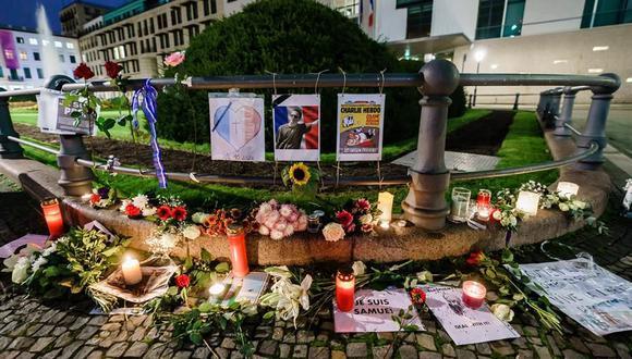 Un improvisado memorial con velas, mensajes y flores en Berlín (Alemania), como homenaje al profesor francés Samuel Paty, decapitado el viernes tras haber mostrado caricaturas de Mahoma en una clase sobre libertad de expresión. (EFE/ Clemens Bilan).