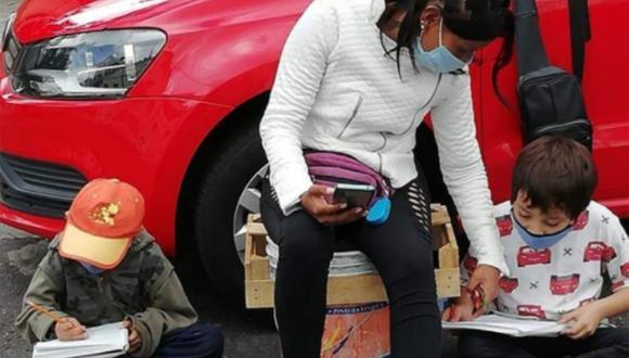 La madre, que trabaja cuidando carros en la calle, ayuda a sus hijos que reciben educación virtual en México. | Foto:  Iztacalco Me Gusta