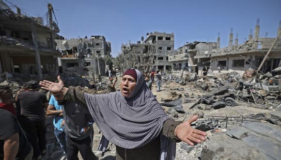 Una mujer palestina reacciona cuando la gente evalúa el daño causado por los ataques aéreos de Israel en Beit Hanun, en el norte de la Franja de Gaza, el 14 de mayo de 2021. (Foto de MAHMUD HAMS / AFP).