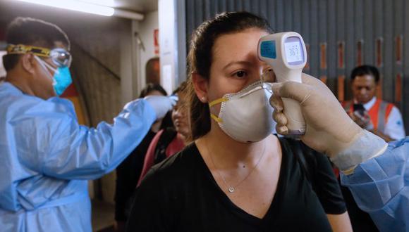 Personal médico controlando la temperatura de los pasajeros a su llegada al Aeropuerto Internacional Jorge Chávez en un vuelo desde España el 11 de marzo de 2020. (Foto de KAREL NAVARRO / Ministerio de Salud de Perú / AFP)