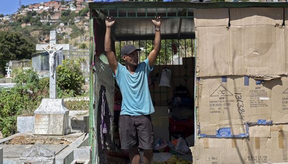 El venezolano Luis Miguel Méndez, de 41 años, se encuentra en la entrada de su refugio improvisado en el cementerio General del Sur de Caracas (Venezuela), el 8 de febrero de 2021. (Pedro Rances Mattey / AFP).