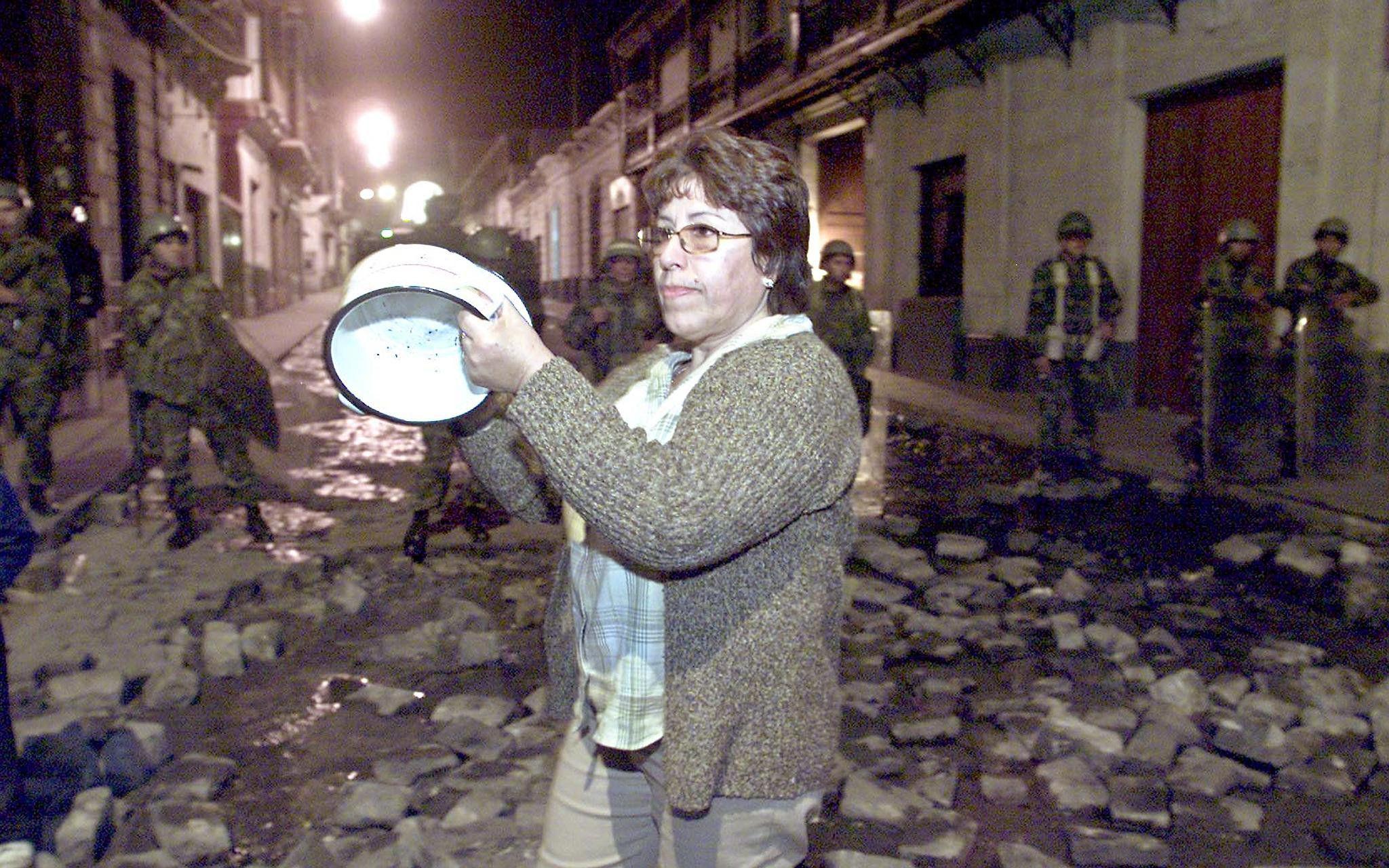 Una mujer golpea una olla frente a soldados del ejercito cerca de la Plaza de Armas de Arequipa, el 18 de junio de 2002, en protesta por el decreto de estado de emergencia y toque de queda en este departamento. La medida se tomo luego que la privatizacion de las estatales Egasa y Egesur provocaron una ola de protestas en este lugar del país. (Foto: Jaime Razuri / AFP)