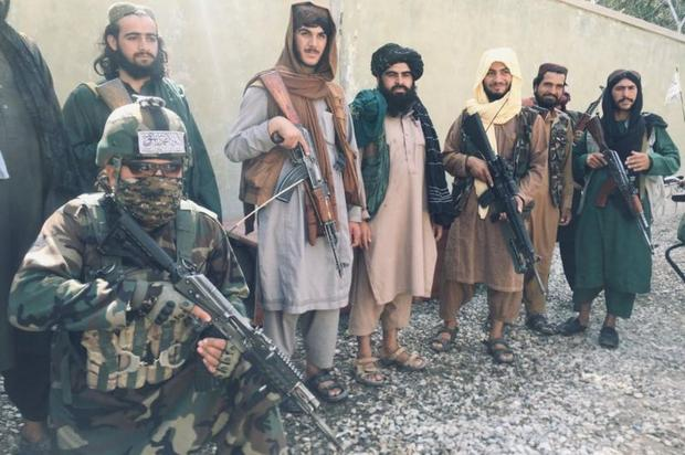 """A member of a Taliban """"red unit"""" (kneeling, lower left) poses with other Taliban in Balkh."""