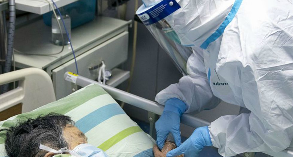 La imagen muestra a una enfermera sosteniendo la mano del paciente para consolarlo mientras está en la UCI. (Foto: Referencial/AFP)