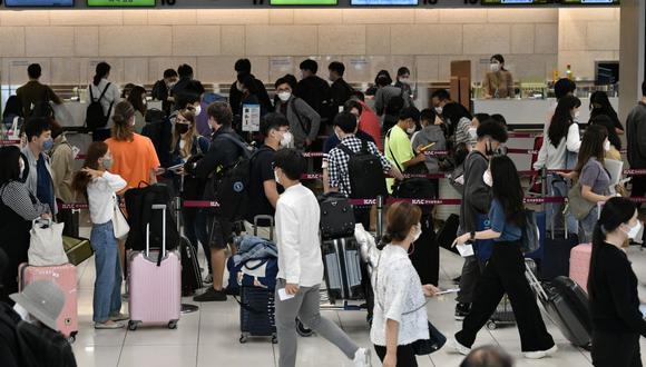 Los viajeros esperan en fila frente a los mostradores de facturación en el aeropuerto de Gimpo en Seúl, Corea del Sur, el 29 de setiembre de 2020. (Jung Yeon-je / AFP).
