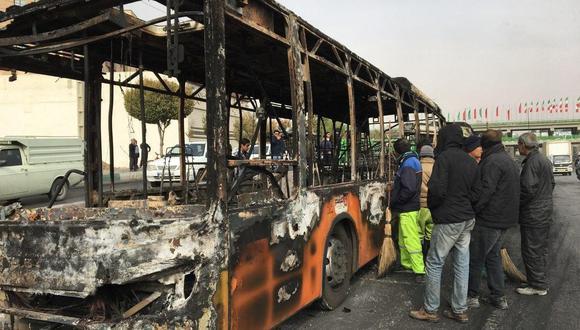 Los iraníes inspeccionan los restos de un autobús que fue incendiado por los manifestantes durante una protesta contra el aumento de los precios de la gasolina en la ciudad central de Isfahan. (AFP).