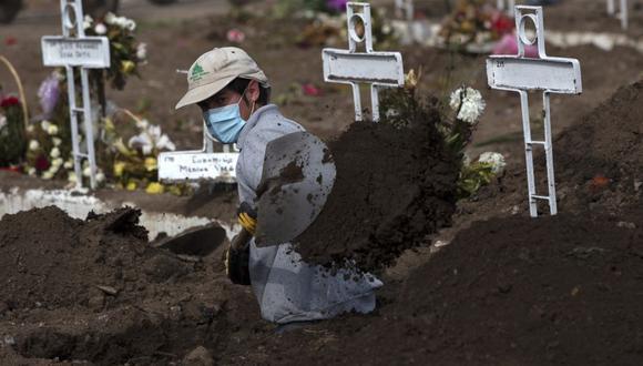 El sepulturero Fernando Quezada, de 27 años, usa una pala mientras trabaja en el Cementerio General de Santiago, el 5 de agosto de 2020, en medio de la pandemia del nuevo coronavirus COVID-19. (Foto: Claudio REYES / AFP).