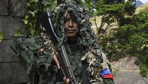 Ismaira Figueroa, francotiradora de la milicia bolivariana, lleva un rifle FAL de calibre 7,62 mm de fabricación belga. (Foto de Yuri CORTEZ / AFP).