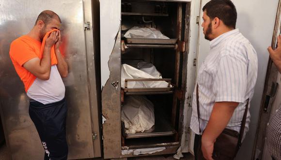 El hermano de Eyad Saleha llora frente a los cadáveres de sus parientes que murieron en un bombardeo de Israel contra su casa en Gaza. (Foto de SAID KHATIB / AFP).