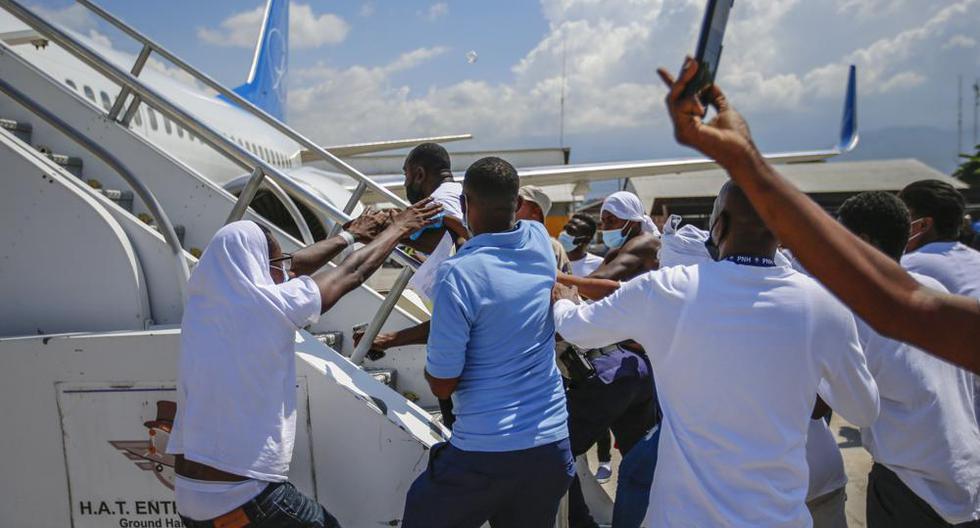 Haitianos deportados de Estados Unidos tratan de subir al mismo avión en el que viajaron su país de origen, en el Aeropuerto Toussaint Louverture, en Puerto Príncipe, Haití, el martes 21 de septiembre de 2021. (AP Foto/Joseph Odelyn).