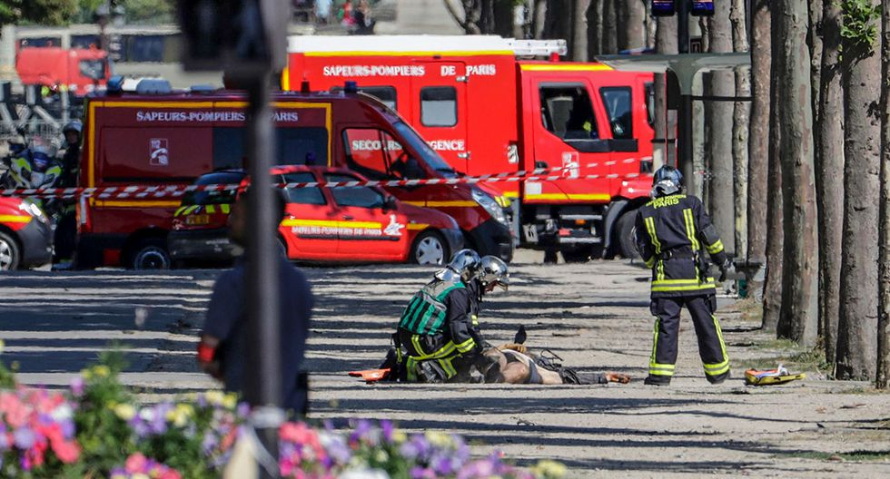 """EDITORS NOTE: Graphic content / Rescuers tend to the body of a man lying in a sealed off area of the Champs-Elysees avenue in Paris, on June 19, 2017 , after a car crashed into a police van before bursting into flames, with the driver being armed, probe sources said. A car burst into flames after it crashed into a police van on the Champs-Elysees avenue in Paris on June 19, police and investigators said, adding that the driver was armed and it appeared to be a """"deliberate"""" act. Authorities said the driver was """"most probably dead"""".  / AFP / Thomas SAMSON"""