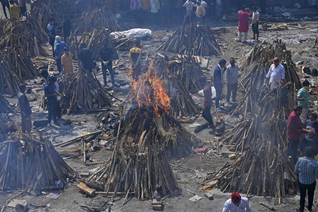 Las familias esperan el turno de la cremación de sus familiares difuntos, envueltos en lienzos blancos.