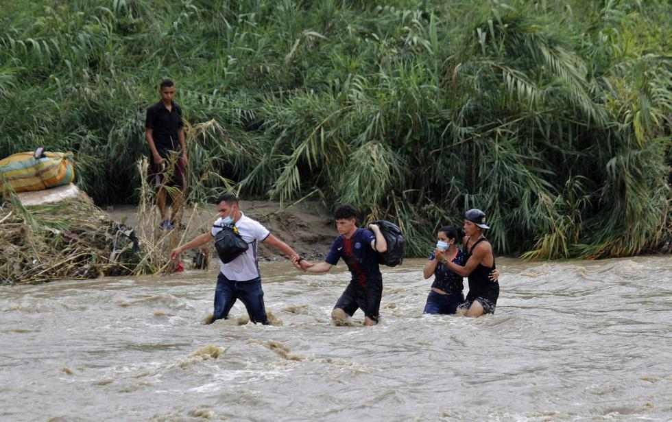 Ciudadanos venezolanos cruzan el fuerte caudal del río Táchira, este jueves, en la ciudad de Cúcuta en un intento por llegar a Colombia. (Foto: SCHNEYDER MENDOZA / AFP)