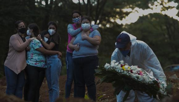 Familiares de una víctima de coronavirus COVID-19 lloran mientras su ser querido es enterrado en el cementerio de Vila Formosa en Sao Paulo, Brasil, el 31 de marzo de 2021. (Foto de Miguel SCHINCARIOL / AFP).