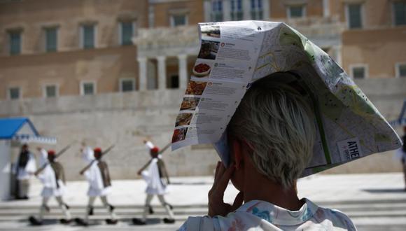 Una mujer se cubre la cabeza con un volante turístico de Atenas para protegerse del sol mientras la Guardia Presidencial griega actúa durante una ola de calor en el centro de Atenas, Grecia. (Foto: EFE / EPA / YANNIS KOLESIDIS).
