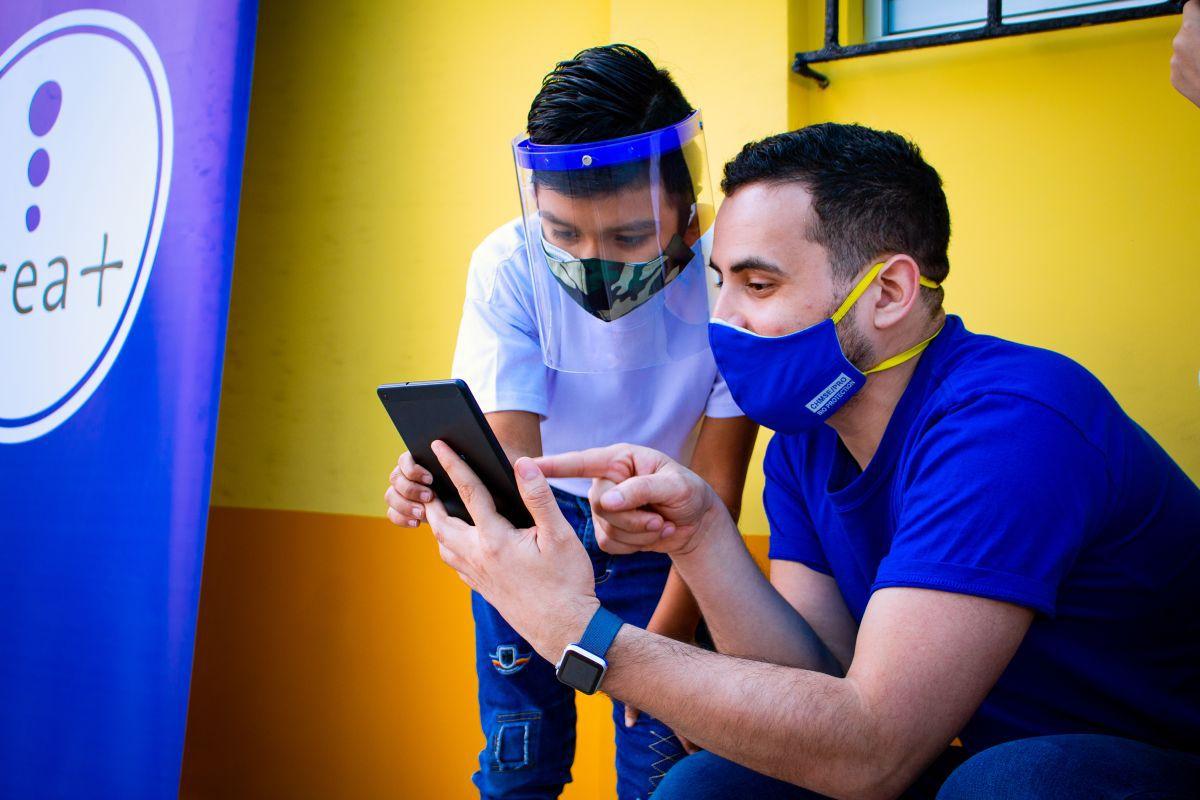 Luis Miguel Starke, director general de Crea+, mostrando el uso de una de las tabletas a un niño. (Foto: Crea+)
