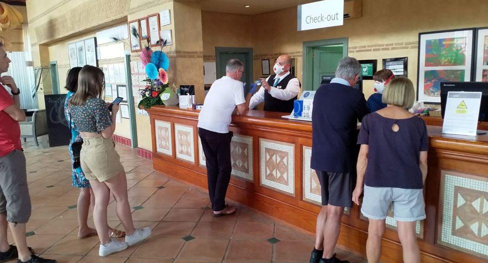 Un empleado utiliza una máscara de protección mientras habla con los huéspedes dentro de un hotel en Tenerife. (AP).