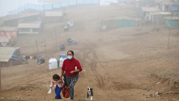 Flor Vera camina entre la neblina con dos de sus seis hijos y su mascota, en el asentamiento humano 6 de Enero. Ella ahora vende tamales entre sus vecinos para subsistir. (Foto: Hugo Curotto/GEC)