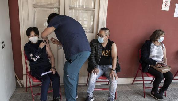 Un trabajador de salud administra una dosis de la vacuna china CoronaVac contra COVID-19 a una mujer en un centro de vacunación en Santiago de Chile, el 22 de abril de 2021. (Foto de Martin BERNETTI / AFP).