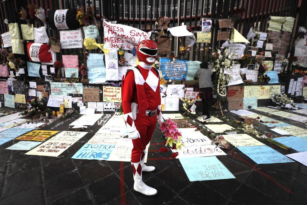 """Un joven disfrazado de """"Power Ranger"""" deja flores en el lugar donde se rinde homenaje a  Inti Sotelo y Jack Pintado en la avenida Abancay. Foto: César Campos / @photo.gec"""