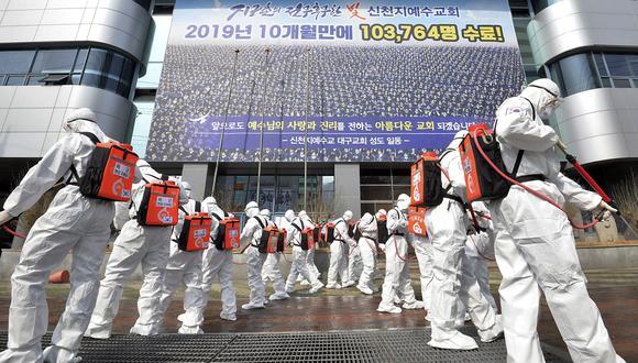 Soldados del ejército de Corea del Sur que usan trajes protectores rocían desinfectante para evitar la propagación del coronavirus frente a una rama de la Iglesia Shincheonji de Jesús en Daegu. (Lee Moo-ryul / Newsis vía AP).