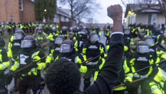 Un hombre levanta el puño mientras encara a los policías estatales de Minnesota que hacen guardia frente a la estación de policía de Brooklyn Center tras la muerte de Daunte Wright, de 20 años. (Foto: Kerem Yucel / AFP):