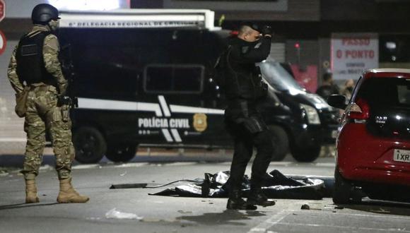 Miembros de la Policía vigilan el local en donde los asaltantes dejaron explosivos escondidos, durante el robo a un banco en la madrugada de este martes, en Criciúma, Brasil. (EFE/ Guilherme Hahn).