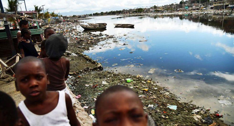 """Desde comienzos de año, a esta joven de 25 años se le ha inundado dos veces su casita y la sola mención del paso de un huracán de categoría cinco por allí, le aterroriza. """"Tengo miedo, pero no solo por mi vida y la de mis hijos, también por todo el mundo, somos todos haitianos, somos como una familia"""", asegura, mientras se aferra fuertemente a su hija de tres años. (Foto: AFP)"""