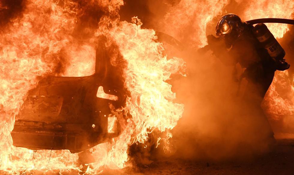 Los bomberos intentan apagar el fuego de un automóvil durante una protesta contra el proyecto de ley de seguridad en París, Francia. (Foto de Alain JOCARD / AFP).