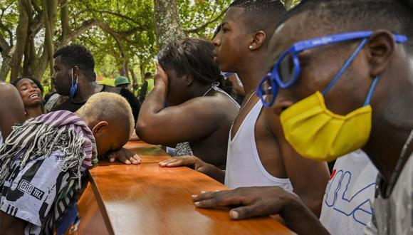 Amigos y familiares lloran ante el ataúd de uno de los cinco jóvenes hallados asesinados en un campo de caña de azúcar en el este de Cali, Colombia, el 13 de agosto de 2020. (Foto de Luis ROBAYO / AFP).
