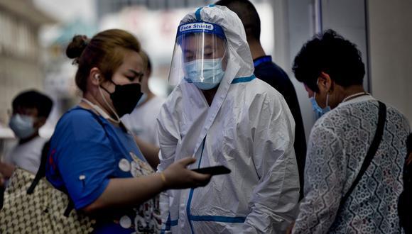 Una mujer conversa con el personal médico en la estación de tren de Shanghái, China. EFE