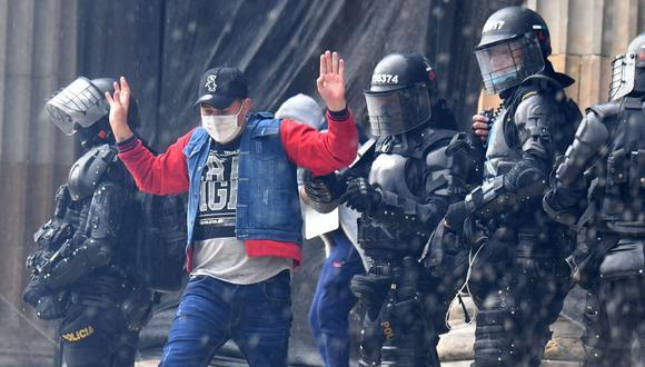 Un manifestante es arrestado por la policía antidisturbios durante una protesta contra el gobierno del presidente Iván Duque en la plaza de Bolívar de Bogotá. (Foto de JUAN BARRETO / AFP).