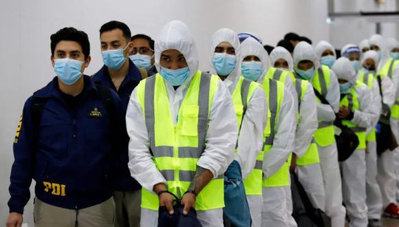 Foto de archivo tomada el 25 de abril de 2021 muestra a migrantes venezolanos listos para abordar un avión mientras son deportados luego de la promulgación de una nueva ley de inmigración que obliga a los migrantes ilegales a salir, en Iquique, Chile. (Foto Referencial: AFP / GOBERNACION TARAPACA / GUSTAVO PAZ).