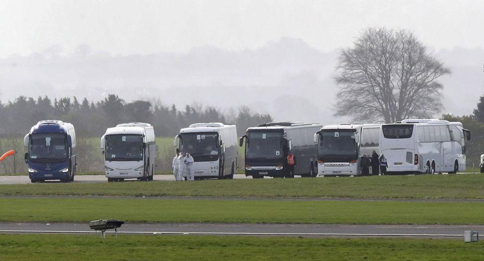 Varios buses esperan a los ciudadanos británicos para recogerlos del avión que partió desde Japón. (AP).