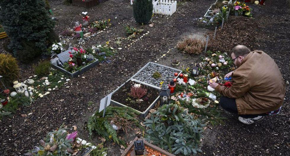 <br>Un visitante enciende una vela en la tumba de su mascota en el cementerio del cementerio Tierhimmel. (AFP)