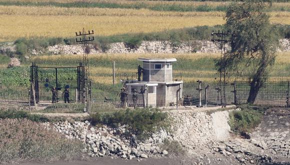 Soldados norcoreanos son vistos en una cerca militar junto a un puesto de guardia en el condado fronterizo norcoreano de Kaepoong, como se ve al otro lado de la Zona Desmilitarizada (DMZ) desde la isla surcoreana de Ganghwa. (YONHAP / AFP)