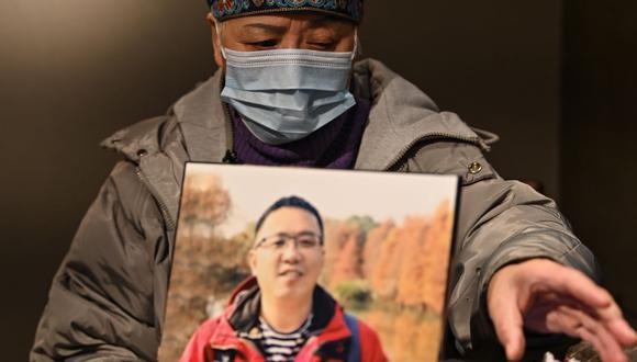 Esta foto tomada el 25 de noviembre de 2020 muestra a Zhong Hanneng hablando durante una entrevista con AFP junto a un retrato de su hijo que murió de coronavirus Covid-19 en Wuhan. (Foto: Hector RETAMAL / AFP).