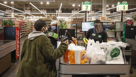 Un cajero atiende a un cliente con una careta protectora en una tienda de Estados Unidos. (Foto Referencial: Archivo/KAMIL KRZACZYNSKI / AFP).